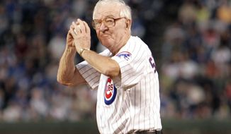 FILE - In this Sept. 14, 2005, file photo, U.S. Supreme Court Justice John Paul Stevens winds up to throw out the first pitch before the start of the Chicago Cubs game with the Cincinnati Reds, at Wrigley Field in Chicago. Retired Supreme Court Justice John Paul Stevens never really put down his pen. Without opinions and dissents to write following his retirement from the Supreme Court in 2010, Stevens chose instead to write books from his home in Florida, reflecting on his life but also the Constitution. (AP Photo/Jeff Roberson, File)