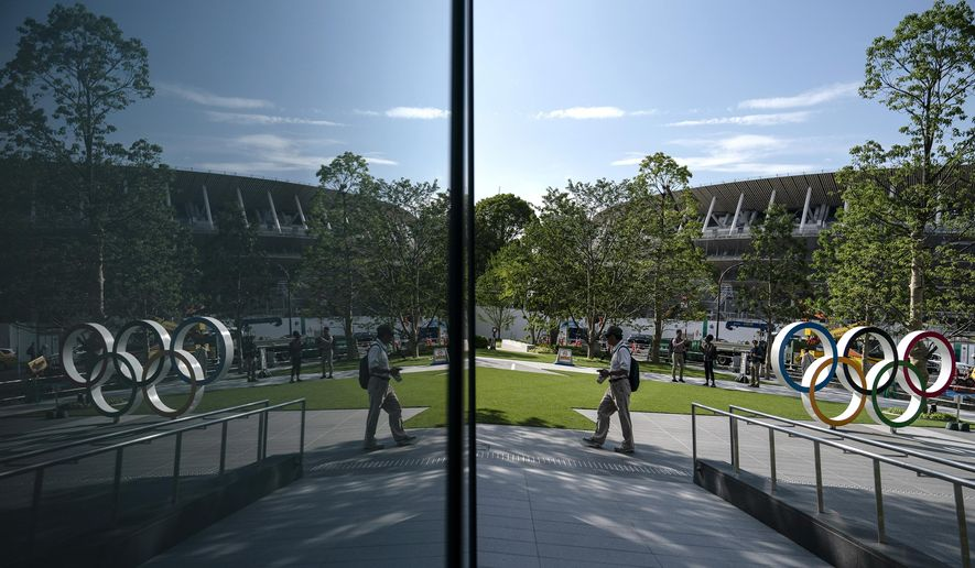 FILE - In this June 17, 2019, file photo, the Olympics rings and New National Stadium are reflected on the facade of a building in Tokyo. The stadium will host the opening and closing ceremonies at the Tokyo 2020 Olympics. (AP Photo/Jae C. Hong, File)