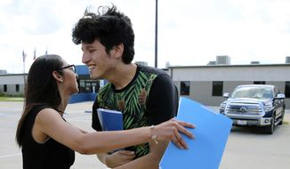 U.S. citizen Francisco Galicia, 18, gets a hug from his attorney, Claudia Galan, after his release from the South Texas Detention Facility in Pearsall, Texas, Tuesday, July 23, 2019. Galicia was released from immigration custody Tuesday after wrongfully being detained for more than three weeks. (Kin Man Hui/The San Antonio Express-News via AP)