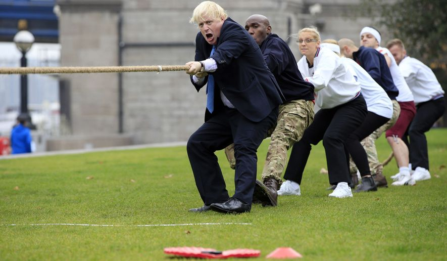 FILE - In this Oct. 27, 2015 file photo Boris Johnson takes part in a tug of war with Armed Forces personnel at the launch of London Poppy Day during his tenure as Mayor of London. (Jonathan Brady/PA via AP, File)