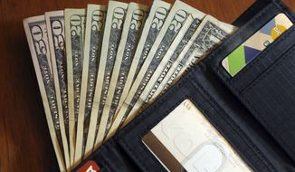 In this June 15, 2018, file photo, cash is fanned out from a wallet in North Andover, Mass. (AP Photo/Elise Amendola, File)