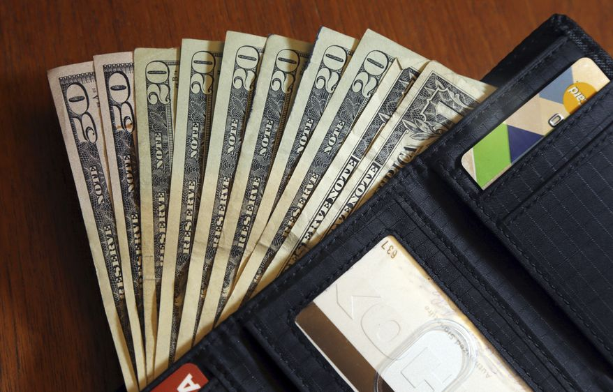 In this June 15, 2018, file photo, cash is fanned out from a wallet in North Andover, Mass. Halfway through the year is an ideal time to check on your finances and prepare for year-end expenses. (AP Photo/Elise Amendola, File)