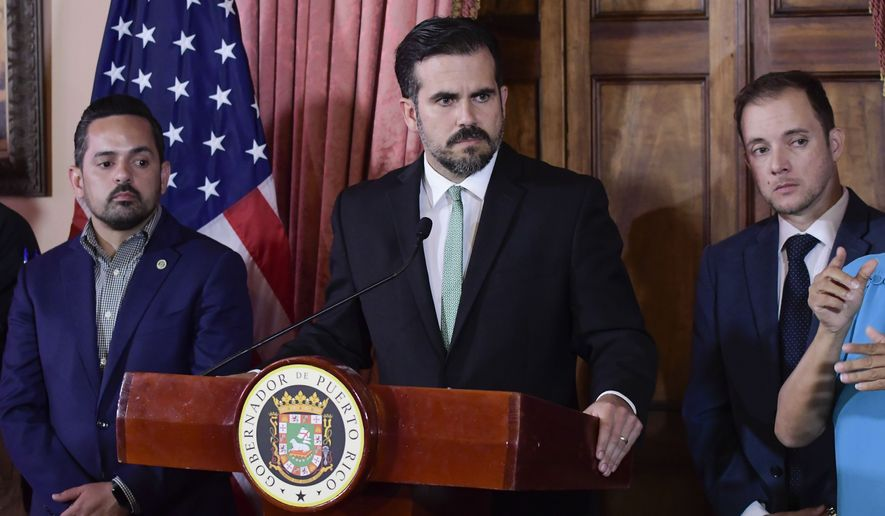 In this July 16, 2019, file photo, Puerto Rico Gov. Ricardo Rossello, accompanied by his Chief of Staff Ricardo Llerandi, right, attends a press conference in La Fortaleza's Tea Room, in San Juan, Puerto Rico. Pictured left is Erik Rolon, undersecretary of the interior. (AP Photo/Carlos Giusti, File)