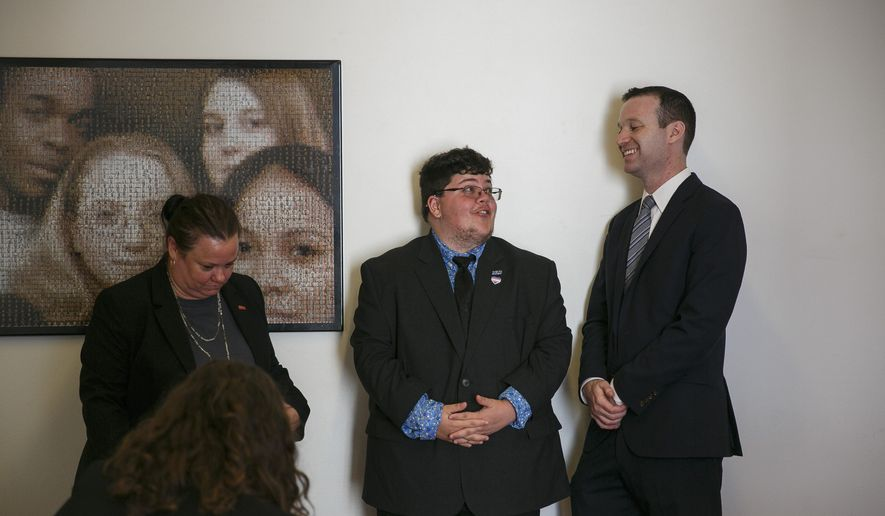 Gavin Grimm, center, a young man who has become a national face for transgender student, speaks with Josh Block, ACLU senior staff attorney before the start of a press conference, Tuesday morning, July 23, 2019, held by The ACLU and the ACLU of Virginia at Slover Library in Norfolk, Va. Grimm, now 20, transitioned from girl to boy before his sophomore year and sued after the Gloucester County School Board banned him from using boys' bathrooms. (Kristen Zeis/The Daily Press via AP)