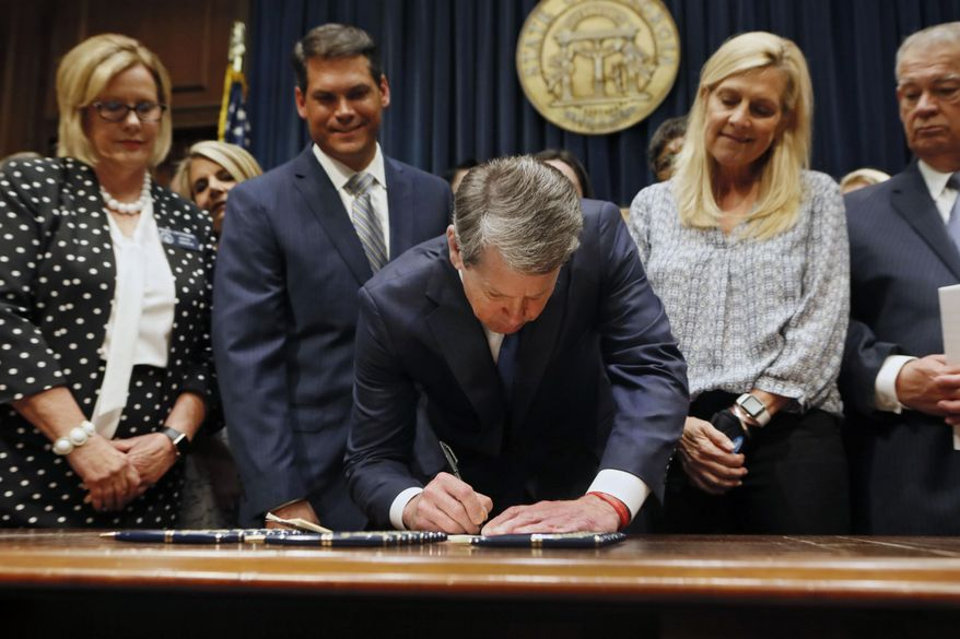 In this May 7, 2019, file photo, Georgia's Republican Gov. Brian Kemp, center, signs legislation in Atlanta, banning abortions once a fetal heartbeat can be detected. Opponents of a Georgia law that bans most abortions are asking a judge Tuesday, July 23, 2019, to keep it from taking effect while a legal challenge plays out. The law is set to become enforceable Jan. 1. Lawyers with the American Civil Liberties Union, Planned Parenthood and the Center for Reproductive Rights sued last month on behalf of Georgia advocacy groups and abortion providers to challenge the measure.  (Bob Andres/Atlanta Journal-Constitution via AP, File)