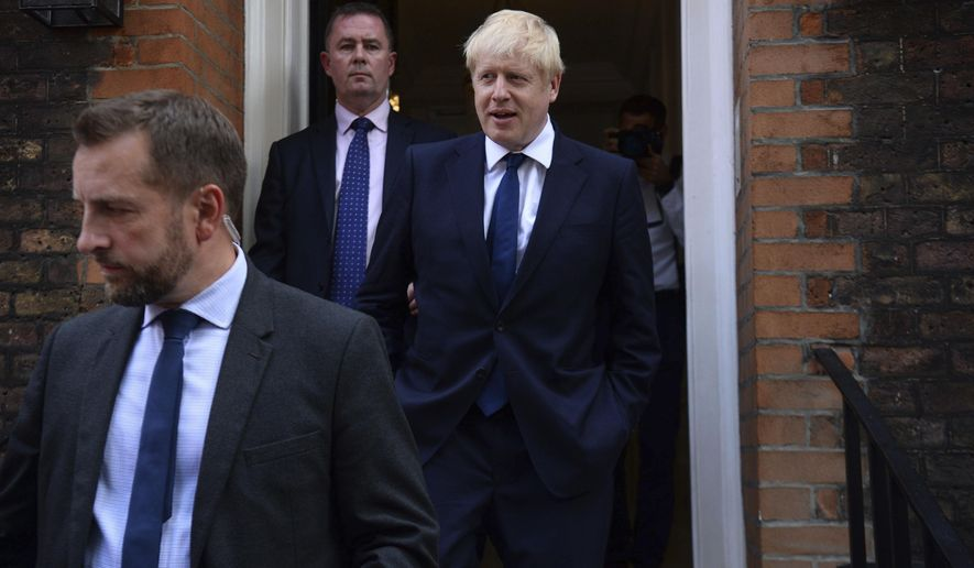 Conservative Party leadership contender Boris Johnson, right, leaves his office in London, Monday July 22, 2019.  Voting closes Monday in the ballot to elect Britain's next prime minister, from the two contenders Jeremy Hunt and Boris Johnson, as critics of likely winner Boris Johnson condemned his vow to take Britain out of the European Union with or without a Brexit deal.(Kirsty O'Connor/PA via AP)