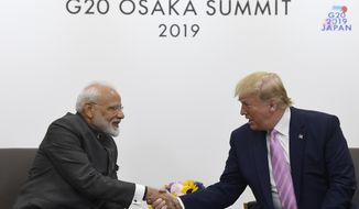 FILE- In this June 28, 2019 file photo, President Donald Trump shakes hands with Indian Prime Minister Narendra Modi, left, during a meeting on the sidelines of the G-20 summit in Osaka, Japan. India's opposition leaders are angrily demanding Modi clarify his position in Parliament about Trump mediating India's long-running dispute with Pakistan over Kashmir. India's External Affairs Minister S. Jaishankar said in Parliament on Tuesday that Modi made no such request to Trump as the U.S. president had claimed. (AP Photo/Susan Walsh, File)