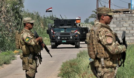 Iraqi security forces conduct a search operation in Taramiyah, 50 kilometers ( 31 miles) north of Baghdad, Iraq, Tuesday, July 23, 2019. Security forces are sweeping villages and farmland north of Baghdad as part of an operation aimed at clearing remaining militants belonging to the Islamic State group from around the country's capital. (AP Photo/Hadi Mizban) ** FILE **
