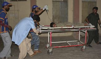 Pakistani volunteers rush an injured boy to a hospital in Quetta, Pakistan, Tuesday, July 23, 2019. A Pakistani official says a roadside bomb has exploded in a market on the outskirts of Quetta, killing several and wounding dozens. (AP Photo/Arshad Butt)