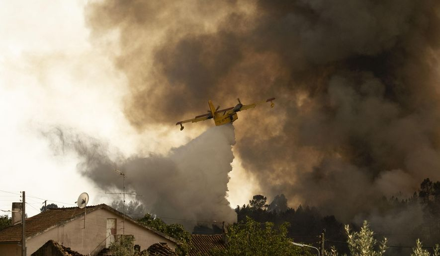 An airplane operates over a fire at the village of Chaveira, near Macao, in central Portugal on Monday, July 22, 2019. More than 1,000 firefighters are battling a major wildfire amid scorching temperatures in Portugal, where forest blazes wreak destruction every summer. About 90% of the fire area in the Castelo Branco district, 200 kilometers (about 125 miles) northeast of the capital Lisbon, has been brought under control during cooler overnight temperatures, according to a local Civil Protection Agency commander. (AP Photo/Sergio Azenha)