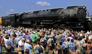People crowd around the newly restored Big Boy No. 4014, the world's largest steam locomotive, as it stopped in Altoona, Wis. on Tuesday, July 23, 2019. (Dan Reiland/The Eau Claire Leader-Telegram via AP)