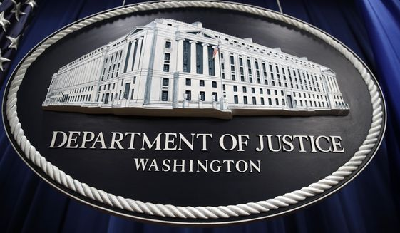 In this Thursday, April 18, 2019, file photo, a sign for the Department of Justice hangs in the press briefing room at the Justice Department, in Washington. (AP Photo/Patrick Semansky, File)  **FILE**