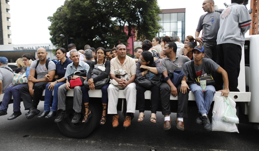People get a ride on the back of a truck during a blackout in Caracas, Venezuela, Monday, July 22, 2019. The lights went out across much of Venezuela Monday, reviving fears of the blackouts that plunged the country into chaos a few months ago as the government once again accused opponents of sabotaging the nation's hydroelectric power system. (AP Photo/Ariana Cubillos)