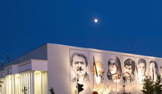 "Zohreh Exhibition Hall at Ashraf 3, dedicated to ""120 Years of the Iranian People's Struggle for Freedom."" The posters on the building, from left: Massoud Rajavi, leader of the Iranian Resistance; the Lion and the Sun, symbol of Iran's safekeeping; Ashraf Rajavi and Moussa Khlabani, two MEK leaders killed in February 1982 in Tehran; Mohammad Hanifnejad, MEK founder; Dr. Hossein Fatemi, foreign minister under the government of Dr. Mossadeq who was executed by the Shahs' regime on Nov. 10, 1954; and Dr. Mohammad Mossadeq, Iran's revered Prime Minister until 1953."