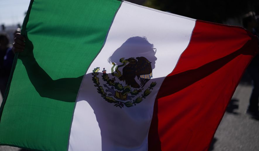 "A demonstrator holds a Mexican flag outside a migrant shelter to protest the presence of thousands of Central American migrants in Tijuana, Mexico, Sunday, Nov. 18, 2018. Protesters accused the migrants of being messy, ungrateful and a danger to Tijuana; complained about how the caravan forced its way into Mexico, calling it an ""invasion,"" and voiced worries that their taxes might be spent to care for the group as they wait possibly months to apply for U.S. asylum. (AP Photo/Ramon Espinosa)"