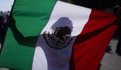 """A demonstrator holds a Mexican flag outside a migrant shelter to protest the presence of thousands of Central American migrants in Tijuana, Mexico, Sunday, Nov. 18, 2018. Protesters accused the migrants of being messy, ungrateful and a danger to Tijuana; complained about how the caravan forced its way into Mexico, calling it an """"invasion,"""" and voiced worries that their taxes might be spent to care for the group as they wait possibly months to apply for U.S. asylum. (AP Photo/Ramon Espinosa)"""