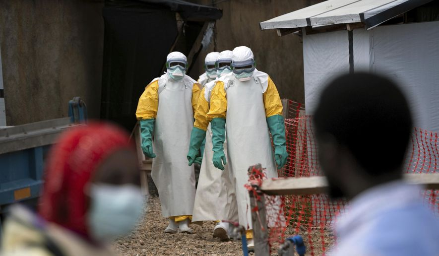 In this Tuesday, July 16, 2019, file photo, health workers wearing protective gear begin their shift at an Ebola treatment center in Beni, Congo. On July 17, the World Health Organization declared the Ebola outbreak an international emergency after it spread to eastern Congo's biggest city, Goma. (AP Photo/Jerome Delay)