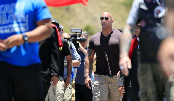 "Actor Dwayne ""The Rock"" Johnson walks on Mauna Kea Access Road during a visit to the protest site against the TMT telescope on Wednesday, July 24, 2019, at the base of Mauna Kea on Hawaii Island. (Jamm Aquino/Honolulu Star-Advertiser via AP)"