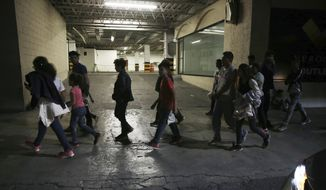 In this July 18, 2019, photo, migrants who have just been bused by Mexican Authorities from Nuevo Laredo to Monterrey, walk off the bus into the street in Monterrey, Mexico. All those taken to Monterrey who spoke with AP said that they had not asked for asylum in the US and some asked to be returned to their home countries, but were told that going to Mexico or remaining in detention were the only options. (AP Photo/Marco Ugarte)