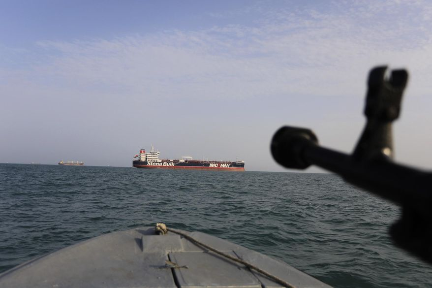 In this Sunday, July 21, 2019, photo, a speedboat of Iran's Revolutionary Guard trains a weapon toward the British-flagged oil tanker Stena Impero, which was seized in the Strait of Hormuz on Friday by the Guard, in the Iranian port of Bandar Abbas. (Morteza Akhoondi/Tasnim News Agency via AP) **FILE**