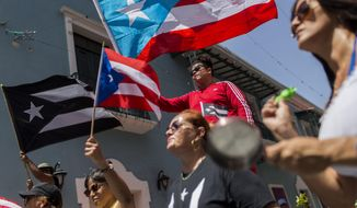 Demonstrators, some waving Puerto Rican national flags, gather in front of the governor's mansion La Fortaleza, in San Juan, Puerto Rico, Wednesday, July 24, 2019. Hundreds of thousands of Puerto Rico have been outraged by leaked, obscenity-laced online chats between Gov. Ricardo Rossello and his advisers, and have protested for nearly two weeks demanding his resignation. (AP Photo/Dennis M. Rivera Pichardo)