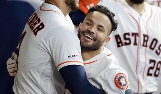 Houston Astros George Springer, left, hugs Jose Altuve, middle, in the dugout as Robinson Chirinos, right, looks on after Altuve's home run during the fifth inning of a baseball game against the Oakland Athletics Wednesday, July 24, 2019, in Houston. (AP Photo/Michael Wyke)