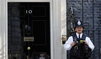 A police officer stands guard outside the Prime Minister's residence of 10 Downing Street in London, Wednesday, July 24, 2019. Boris Johnson will replace Theresa May as Britain's Prime Minister later Wednesday, following her resignation last month after Parliament repeatedly rejected the Brexit withdrawal agreement she struck with the European Union. (AP Photo/Frank Augstein)