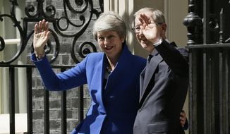 Britain's Prime Minister Theresa May and her Husband Philip May wave from the steps of 10 Downing Street, as they leave to visit Queen Elizabeth II, where she will officially resign as Prime Minister, in London, Wednesday, July 24, 2019. Boris Johnson will replace May as Prime Minister later Wednesday. (AP Photo/Tim Ireland)
