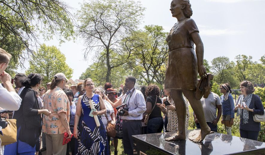 In this Tuesday, July 23, 2019 photo, Sally Liuzzo-Prado, front in blue, reacts during the unveiling of the new Viola Liuzzo statue by Austen Brantley, dedicated to her mother and civil rights activist, at Viola Liuzzo Park in Detroit. Liuzzo was slain in Alabama during a 1965 voting rights march.  (Kathleen Galligan/Detroit Free Press via AP)