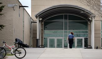 FIE - In this April 17, 2019, file photo, a police officer walks to the front doors of Columbine High School in Littleton, Colo., where two students killed 12 classmates and a teacher in 1999. The Jefferson County School District has abandoned a proposal to demolish Columbine and replace it after a community survey showed strong opposition to the idea. (AP Photo/Joe Mahoney, File)