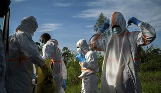 In this Sunday, July 14, 2019, file photo, burial workers put on protective gear before carrying the remains of Mussa Kathembo, an Islamic scholar who had prayed over those who were sick, and his wife, Asiya, to their final resting place in Beni, Congo. Both died of Ebola. (AP Photo/Jerome Delay)