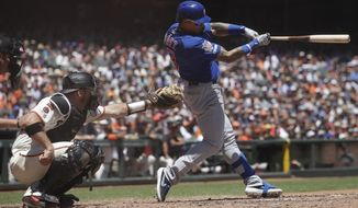 Chicago Cubs' Javier Baez, right, hits a double in front of San Francisco Giants catcher Stephen Vogt during the third inning of a baseball game in San Francisco, Wednesday, July 24, 2019. (AP Photo/Jeff Chiu)