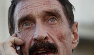 FILE - In this Dec. 4, 2012 file photo, software company founder John McAfee talks on his mobile phone after a press conference outside the Supreme Court in Guatemala City. Authorities in the Dominican Republic said Wednesday, July 24, 2019, that McAfee was arrested aboard a yacht carrying high-caliber weapons, ammunition and military-style gear, but McAfee tweeted later Wednesday that he and five others who had been released from detention. (AP Photo/Moises Castillo, File)