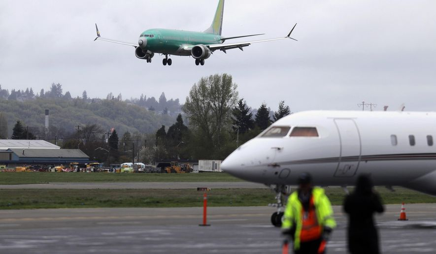 FILE - In this April 10, 2019, file photo a Boeing 737 MAX 8 airplane being built for India-based Jet Airways, top, lands following a test flight, Wednesday, April 10, 2019, at Boeing Field in Seattle. Boeing Co. reports earning on Wednesday, July 24, 2019. (AP Photo/Ted S. Warren, File)