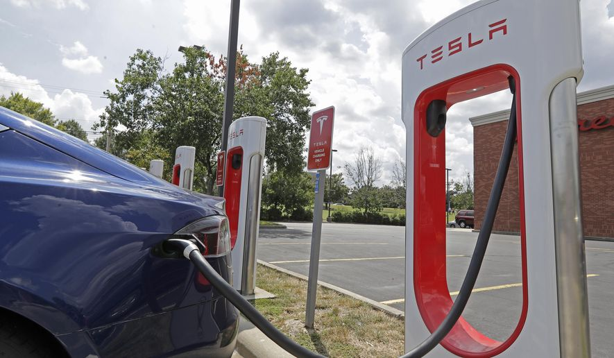 In this July 19, 2019, photo a Tesla vehicle charges at a Tesla Supercharger site in Charlotte, N.C. Tesla, Inc. reports earning on Wednesday, July 24, 2019. (AP Photo/Chuck Burton)