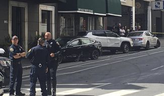 FILE - This Sunday, July 21, 2019 file photo, and provided by KGO-TV shows the scene after a woman was arrested after running a red light in a rented Tesla in San Francisco and causing a crash that killed a tourist and left his wife critically injured. San Francisco police said Wednesday, July 24, 2019, preliminary information shows a rented Tesla that was speeding when it ran a red light and struck a couple, was not on semi-autonomous Autopilot mode. (Kate Larsen/KGO-TV via AP,File)