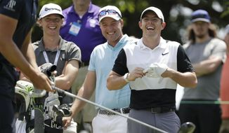 Rory McIlroy, of Northern Ireland, right, and Philip Eriksson, of Sweden, second from right, laugh as they watch Henrik Stenson, of Sweden, get ready to hit in a left-handed driving contest on the 13th hole during a practice round for the World Golf Championships-FedEx St. Jude Invitational Wednesday, July 24, 2019, in Memphis, Tenn. (AP Photo/Mark Humphrey)