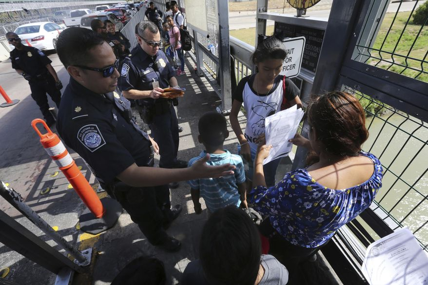In this July 17, 2019, file photo, a United States Customs and Border Protection Officer checks the documents of migrants before being taken to apply for asylum in the United States, on International Bridge 1 in Nuevo Laredo, Mexico. (AP Photo/Marco Ugarte, File)