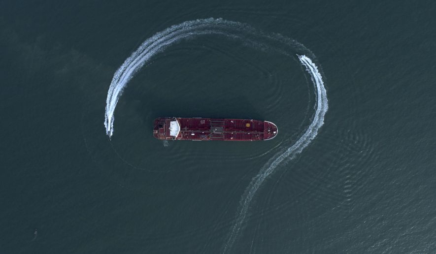 In this Sunday, July 21, 2019, photo, an aerial view shows a speedboat of Iran's Revolutionary Guard moving around the British-flagged oil tanker Stena Impero, which was seized in the Strait of Hormuz on Friday by the Guard, in the Iranian port of Bandar Abbas. (Morteza Akhoondi/Tasnim News Agency via AP)