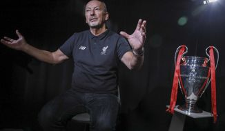 Liverpool soccer chief executive officer Peter Moore gestures during an interview Wednesday, July 24, 2019, in New York. At right is the 2019 Champions League championship trophy. (AP Photo/Bebeto Matthews)