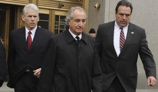 In this March 10, 2009, photo, Bernard Madoff, center, exits Manhattan federal court in New York. Madoff, who pleaded guilty in 2009 to orchestrating the largest Ponzi scheme in history, is seeking an early release from prison. The Department of Justice confirmed on Wednesday, July 24, 2019, that Madoff has a pending request to get his 150-year sentence reduced. (AP Photo/Louis Lanzano) **FILE**