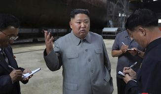 """FILE - In this undated file photo provided on Tuesday, July 23, 2019, by the North Korean government, North Korean leader Kim Jong Un, center, speaks while inspecting a newly built submarine to be deployed soon, at an unknown location in North Korea. North Korea fired two unidentified projectiles into the sea on Thursday, July 25, South Korea's military said, the first launches in more than two months as North Korean and U.S. officials work to restart nuclear diplomacy. Independent journalists were not given access to cover the event depicted in this image distributed by the North Korean government. The content of this image is as provided and cannot be independently verified. Korean language watermark on image as provided by source reads: """"KCNA"""" which is the abbreviation for Korean Central News Agency. (Korean Central News Agency/Korea News Service via AP, File)"""