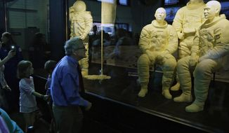 Ohio Gov. Mike DeWine takes his grandchildren Steven Dudukovich, 6, and Jean Dudukovich, 8, to see the butter sculptures of astronauts Neil Armstrong, Buzz Aldrin and Michael Collins in the Dairy Products Building inside the Ohio State Fair in Columbus, Ohio, after the opening on Wednesday, July 24, 2019. (Kyle Robertson/The Columbus Dispatch via AP)