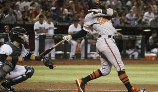 Baltimore Orioles' Dwight Smith Jr., right, watches the flight of his three-run home run as Arizona Diamondbacks catcher Alex Avila, left, looks on during the third inning of a baseball game Tuesday, July 23, 2019, in Phoenix. (AP Photo/Ross D. Franklin)