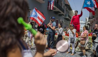 Demonstrators, some waving Puerto Rican national flags, chant in front of the governor's mansion La Fortaleza, in San Juan, Puerto Rico, Wednesday, July 24, 2019. Hundreds of thousands of Puerto Rico have been outraged by leaked, obscenity-laced online chats between Gov. Ricardo Rossello and his advisers, and have protested for nearly two weeks demanding his resignation. (AP Photo/Dennis M. Rivera Pichardo)