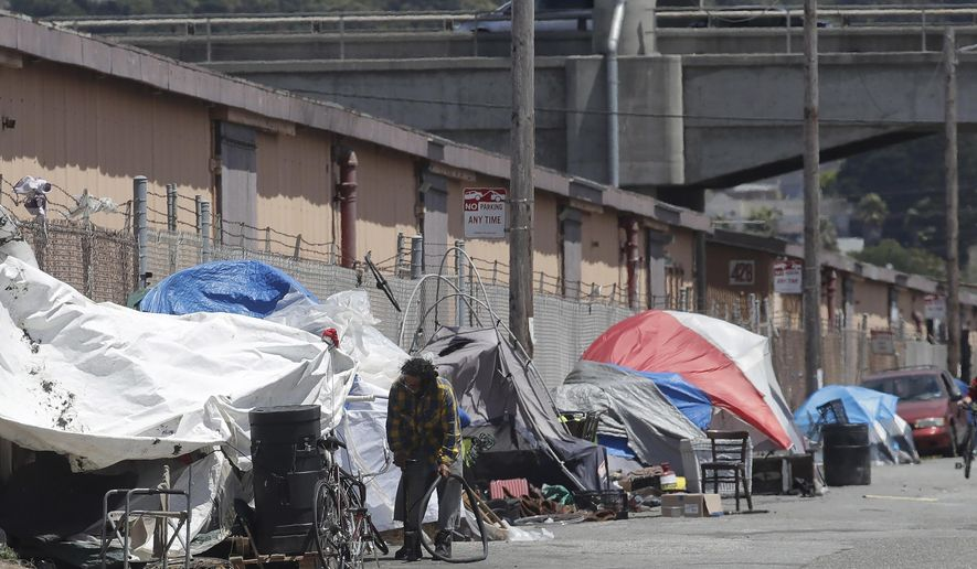 FILE - This Thursday, June 27, 2019, photo shows a man holding a bicycle tire outside of a tent along a street in San Francisco. San Franciscans should put aside their political differences and support finding homes for more than 1,000 homeless people, according to a public engagement campaign beginning Thursday, July 25, 2019. (AP Photo/Jeff Chiu, File)