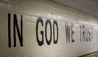"""In God We Trust"" is stenciled in a wall at South Park Elementary in Rapid City, South Dakota in this July 23, 2019 photo. When students return to public schools across South Dakota this fall there should be a new message displayed in a common area, a cafeteria, entryway or other prominent location. A new state law that took effect this month requires all public schools in the state's 149 districts to paint, stencil or otherwise display the national motto ""In God We Trust."" The South Dakota lawmakers who proposed the law said the requirement was meant to inspire patriotism in the state's public schools.(Adam Fondren/Rapid City Journal via AP)"
