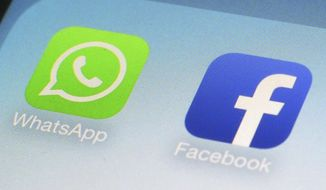 FILE - This Feb. 19, 2014, file photo, shows WhatsApp and Facebook app icons on a smartphone in New York. Is Big Tech headed for a big breakup? Federal regulators are already investigating Facebook's privacy practices. And the antitrust question has been rumbling in the background, with critics calling for spinning off WhatsApp and Instagram. (AP Photo/Patrick Sison, File)