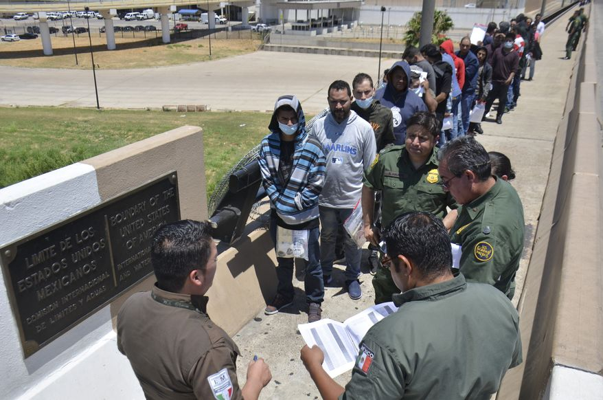 "United States Border Patrol officers return a group of migrants back to the Mexico side of the border as Mexican immigration officials check the list, in Nuevo Laredo, Mexico, Thursday, July 25, 2019. Mexico has received some 20,000 asylum seekers returned to await U.S. immigration court dates under the program colloquially known as ""remain in Mexico."" (AP Photo/Salvador Gonzalez)"