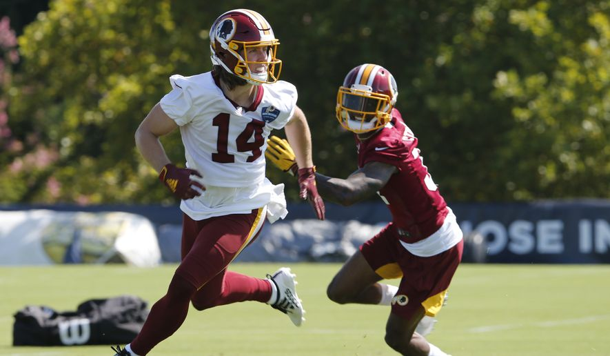 Washington Redskins wide receiver Trey Quinn (14) looks for the pass as cornerback Greg Stroman (37) defends during the first day of NFL football training camp in Richmond, Va., Thursday, July 25, 2019. (AP Photo/Steve Helber) **FILE**